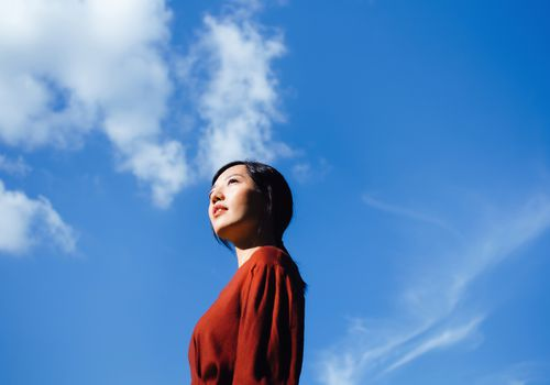 Low angle portrait of confident young Asian woman standing against beautiful clear blue sky, looking up to sky enjoying sunlight. Freedom in nature. Connection with nature - stock photo