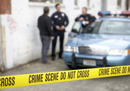 Male police officers standing behind crime scene tape