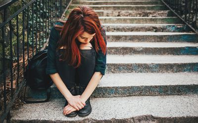 Sad lonely girl sitting on stairs