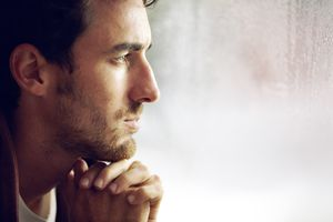 man looking contemplatively out a window