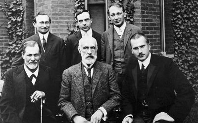 six famous psychologists posing in front of college building