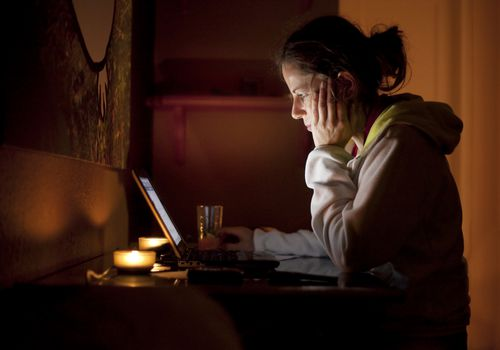 Woman using a laptop in a darkened room