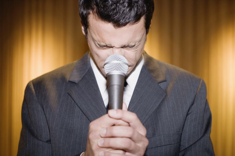 Man closing eyes behind microphone