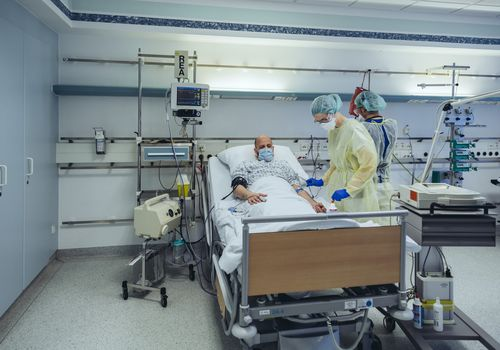 Doctors caring for patient in emergency care unit of a hospital taking blood sample