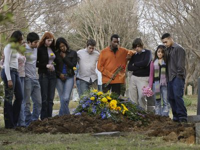 A group of young adults congregate around the grave of a friend who died from drugs