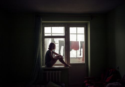 Depressed woman sits in a dark rooms by the window