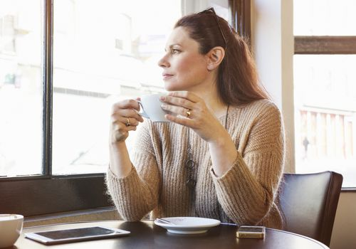 Woman thinking with coffee