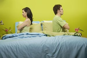 Angry couple sitting back to back on bed