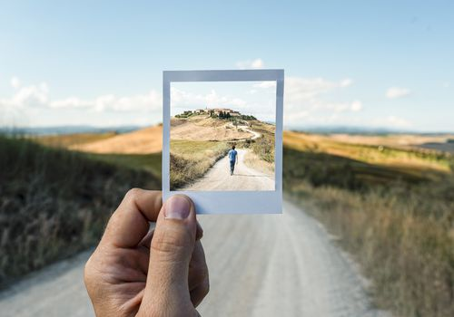 See-through photograph with man walking along a road.