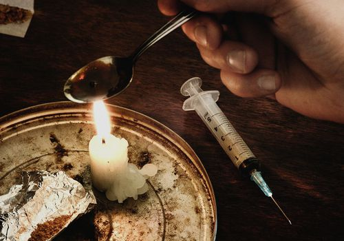 Hand cooking heroin on a spoon over a candle flame