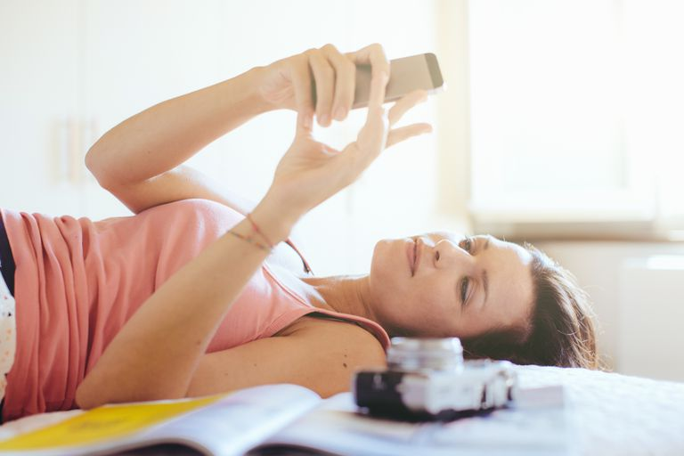 Woman relaxing with phone for stress management.