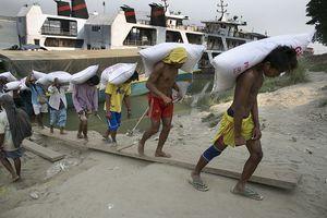 Burmese men struggle to unload heavy cargo from boats.