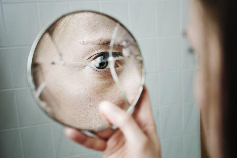 woman looking at herself in a broken mirror
