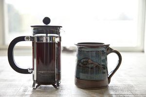 Coffee plunger and mug on table