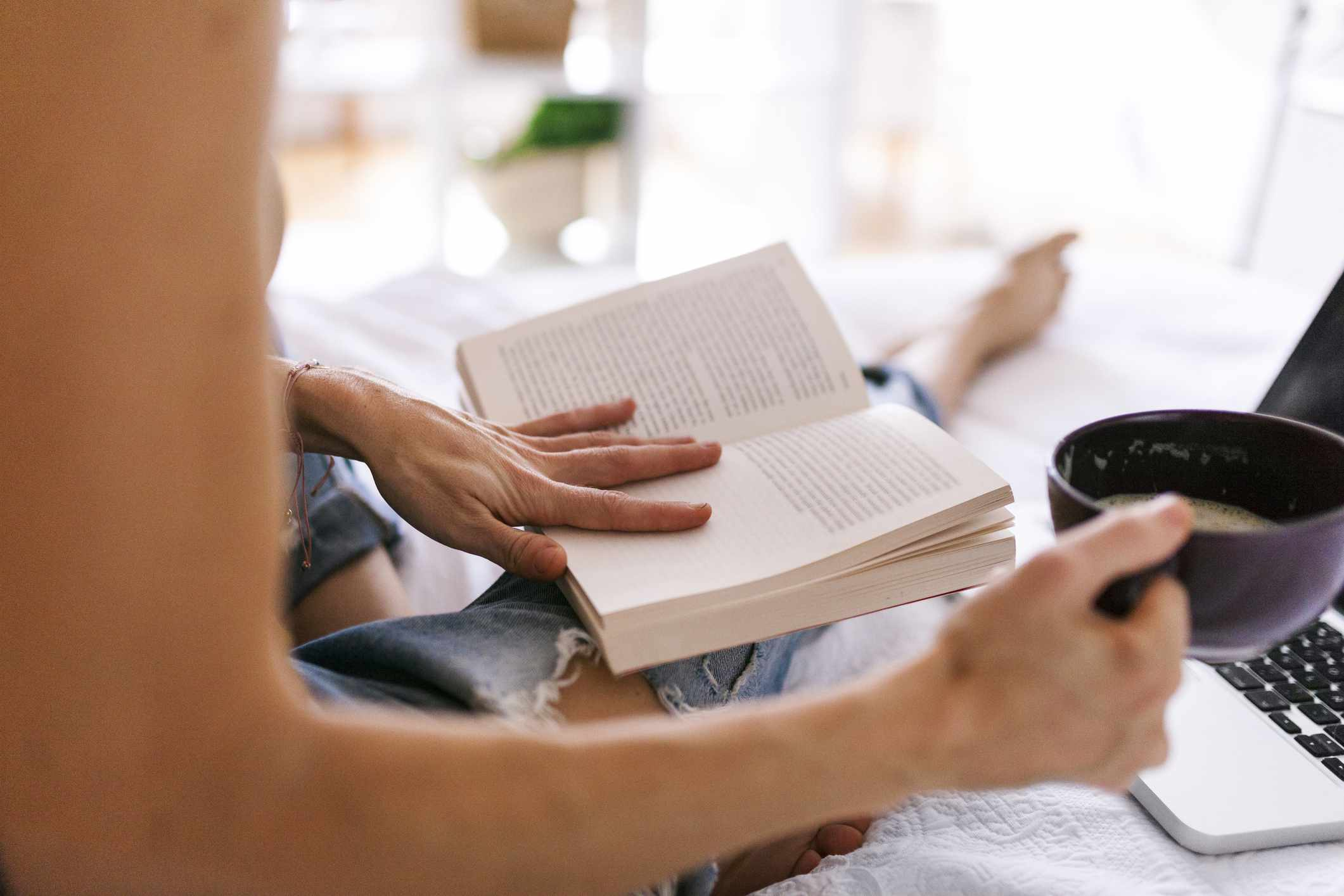 A woman sitting on a bed, reading a book with her laptop open a cup of coffee in her hand.
