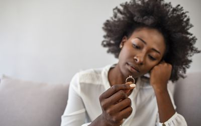 Upset depressed young woman holding wedding ring indoors