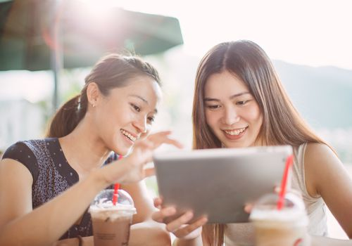 Two women drinking frozen coffee drinks and looking at a tablet