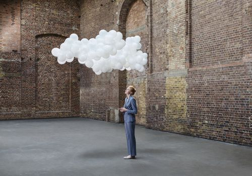 woman standing under a thought cloud in a room with brick walls