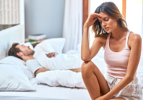 Distressed woman sitting at the edge of the bed while husband sleeps