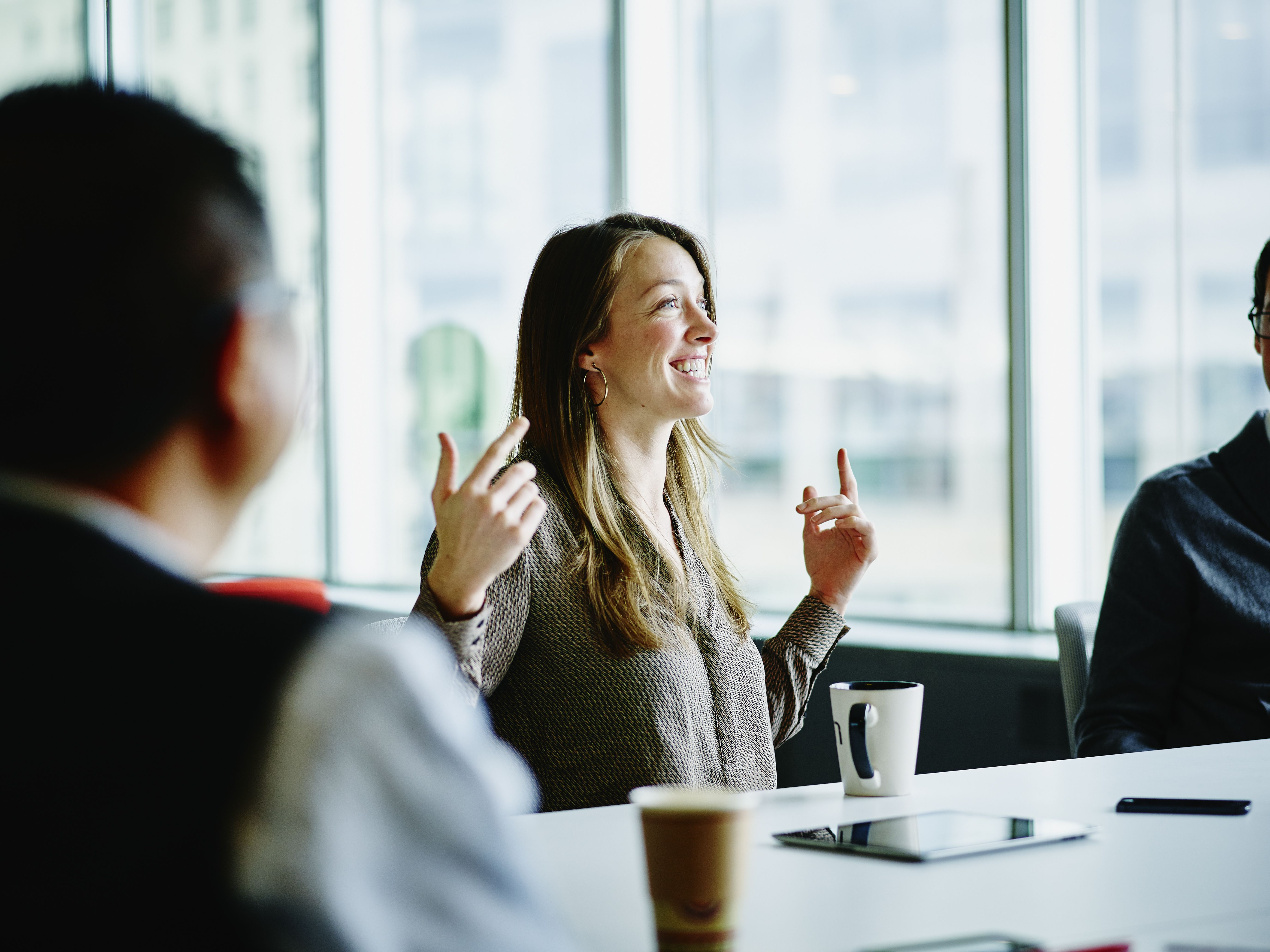 woman smiling and talking in office boardroom
