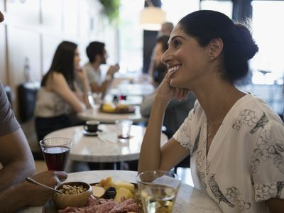 Woman smiling at boyfriend, eating and drinking wine at cafe table