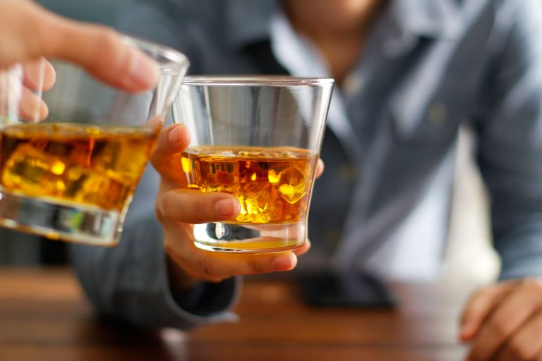 Close-up two men clinking glasses of whiskey drink alcohol beverage together at counter in the pub
