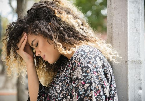 Mixed race woman rubbing her forehead in pain