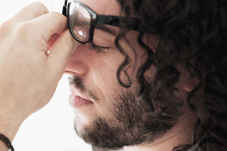Stressed Caucasian man rubbing his eyes