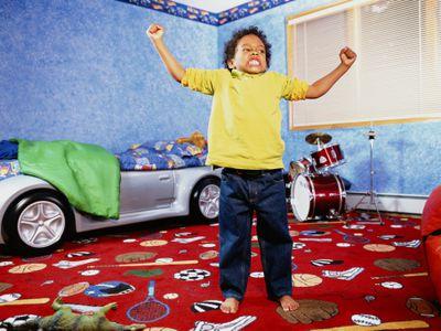Boy (4-6) posing in bedroom, portrait