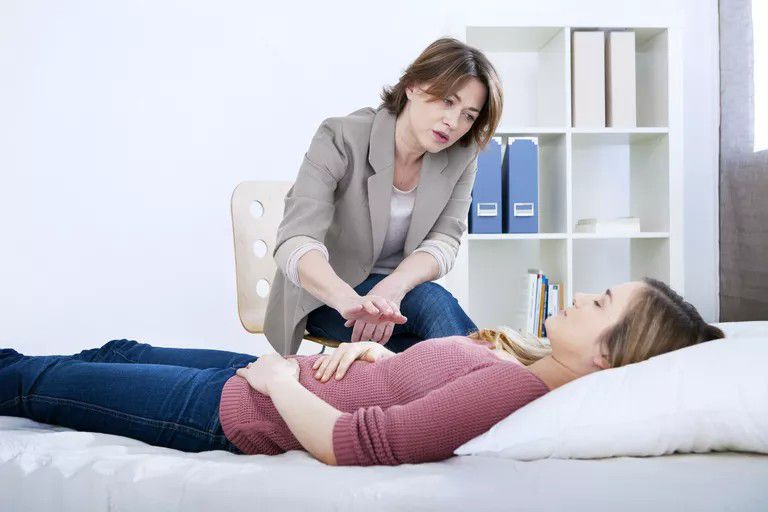 Female therapist guiding patient through hypnotherapy