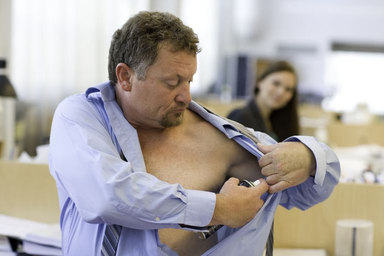 Mature man applying deodorant in office
