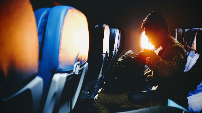 long distance relationship -- man in airplane looking into his luggage with sunset through the window