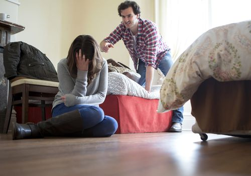 Man yelling at woman who is hiding her head in her hands, sitting on the floor
