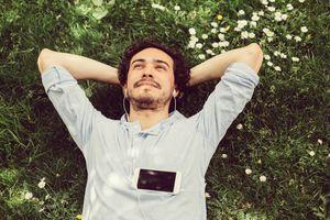 Man lying in grass meditating