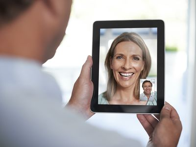 man and woman talking over tablet
