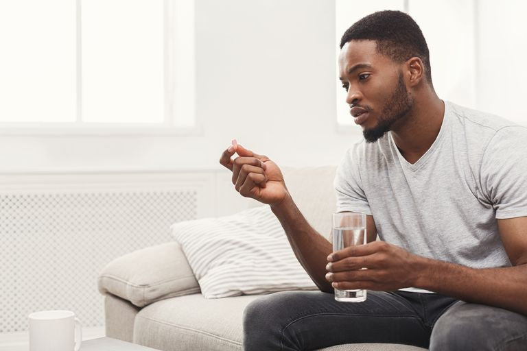 Serious man ready to take a pill sitting on couch