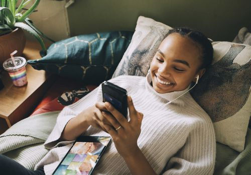 Young woman smiling and looking at her phone.