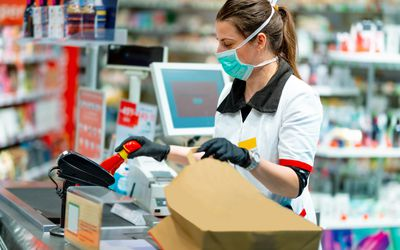 woman working at grocery store wearing protective mask