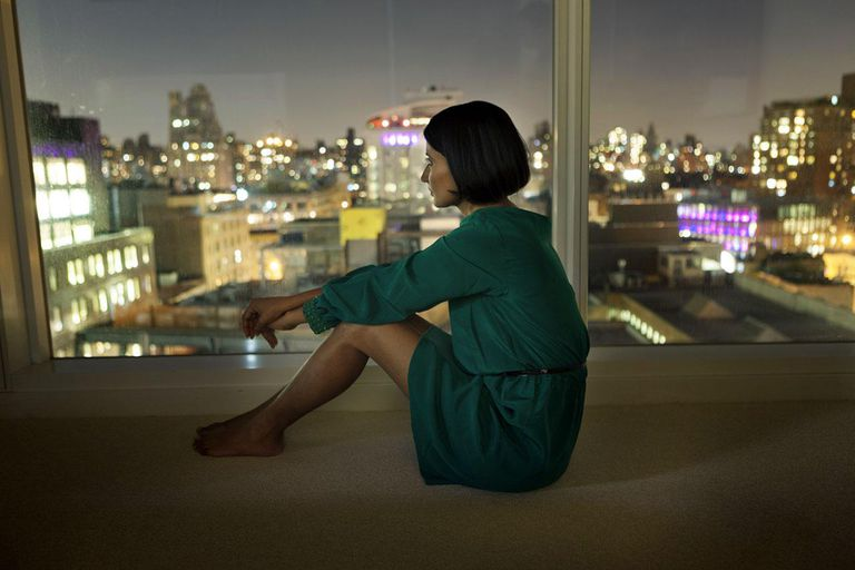 Woman looking out a picture window at night
