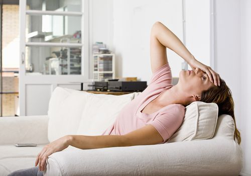 Woman leaning back on a couch with her hand on her head