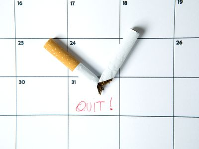 Cigarette snapped in half on top of a calendar with