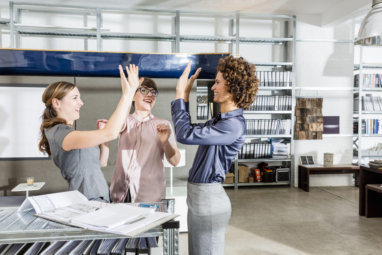 Boss high fiving female employees