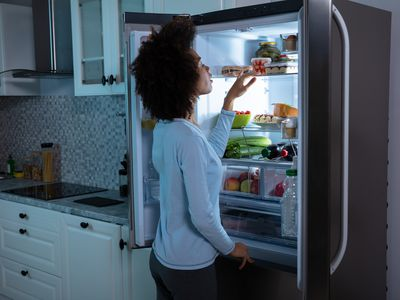 Woman Searching Food In Refrigerator