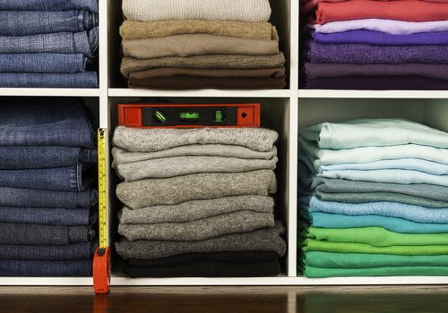 Neatly organized clothing in cubicles with spirit level and ruler
