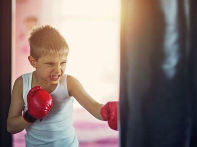 Little boy wearing boxing gloves hitting punching bag