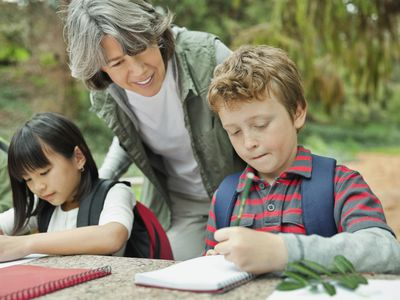 Students making notes at picnic table while adult woman looks on