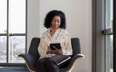 Therapist looks down at tablet while sitting in chair in room with large windows