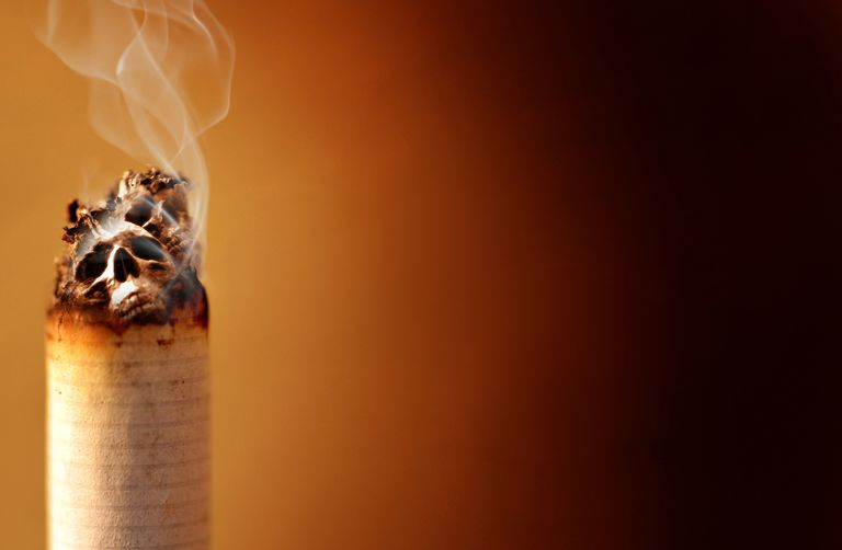 Close-up of the burning end of a cigarette with skulls in the ashes