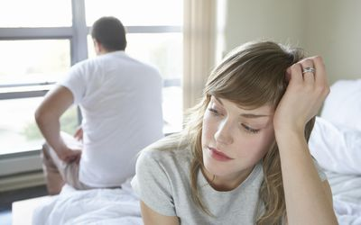 Couple sitting on bed discussing reasons for cheating
