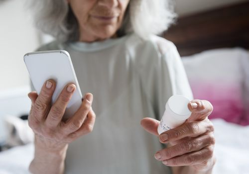 Older woman holding smartphone in one hand and pill bottle in another